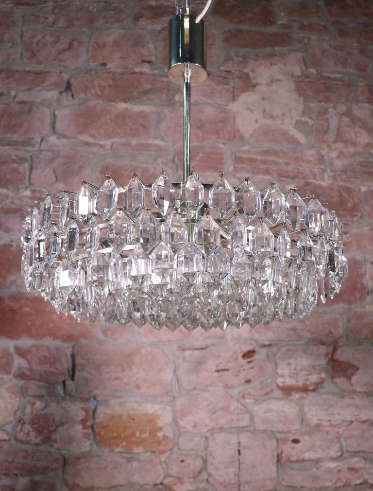 Large and very impressive chandelier with faceted crystals on a silver plated frame. Made in Austria in the 1960s. Measures: diameter 55 cm / 21.65 in., height 20 cm / 7.87 in., ceiling height including suspension 57 cm / 22.4 in. The lamp takes six
