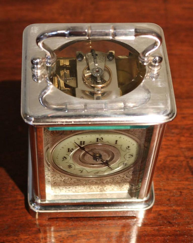 An attractive silver plated carriage clock dating to the late Victorian period. It has a corniche case, with a large bevel edge oval top window. It has an enamel chapter ring and a finely engraved floral dial mask. The 8 day movement has a cylinder