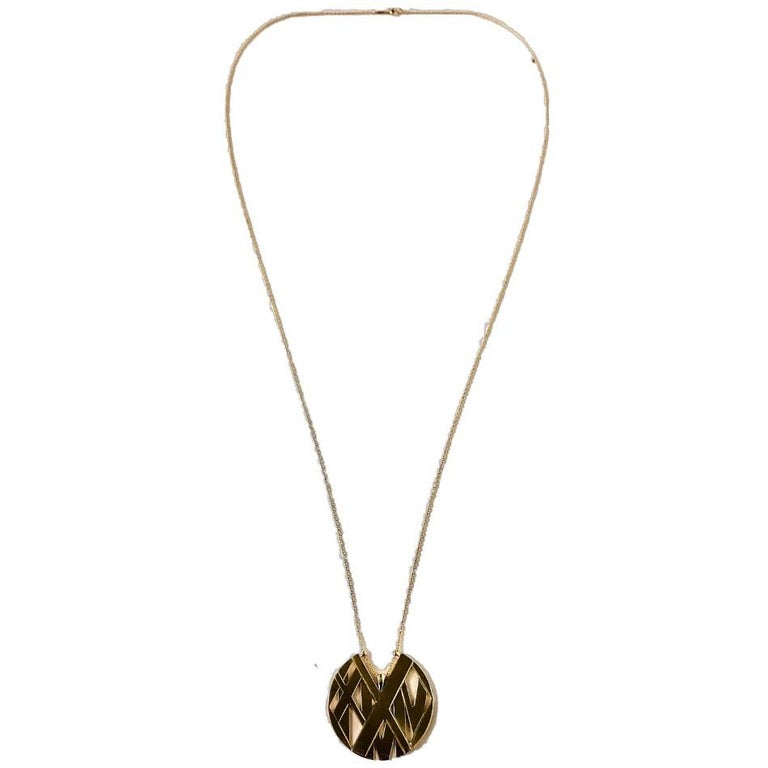This large, distinctive and not often seen 18k yellow gold Tiffany Atlas pendant on 36 inch Tiffany & Co. neck chain is exquisite in it's simplicity. It displays several layers of Roman Numerals  that form a round disc measuring 1 3/4 inches in