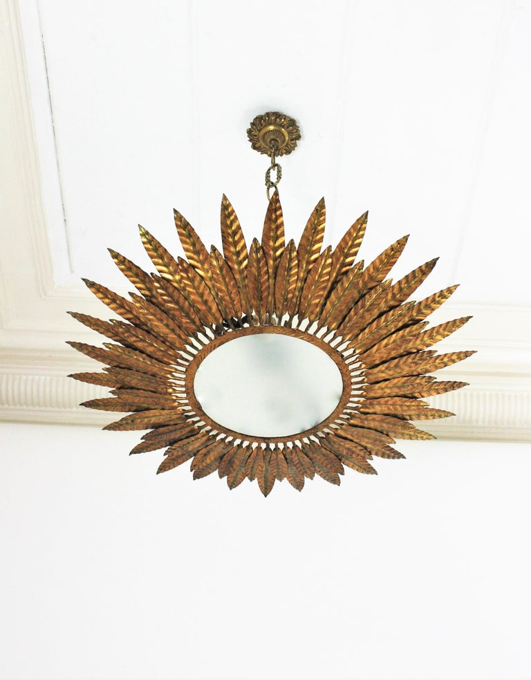 Mid-Century Modern gilt iron sunburst flush mount or pendant with leaf motifs surrounding a central frosted glass diffuser, Spain, 1950s. Handcrafted in hammered iron with gold leaf finishing. Nice aged patina and glamorous original gold leaf