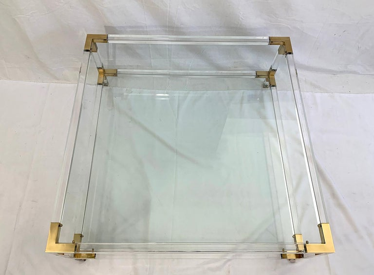 Large coffee table with two glass shelves in the style of Charles Hollis or Maison Jansen, The windows are removable and the frame is made of Lucite with corners in polished brass. Manufacture, circa 1970.  The glass can be replaced for 200