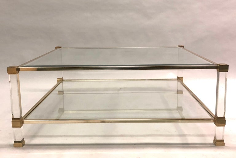 A large, square, French Mid-Century Modern, double level cocktail table in Lucite and brass by Pierre Vandel. The square form of this table is rare and highly desirable for chic look and practical applications.
