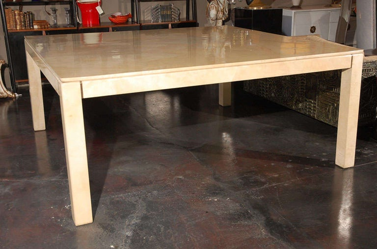 An impressive parchment dining table by Karl Springer. Brass detail on the apron on either side of each leg. Leg clearance is 26 3/4