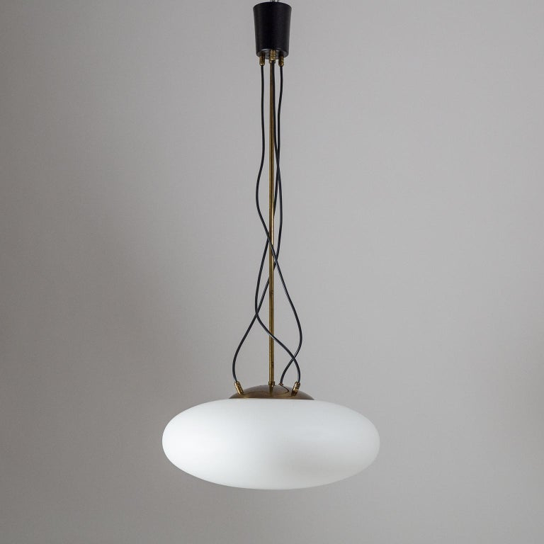 Striking Stilnovo pendant or chandelier from the 1950s. A large disc-shaped satin glass diffuser is suspended by brass hardware with three cables/wires free-flowing from the canopy into the brass cover of the glass body. Very nice original condition