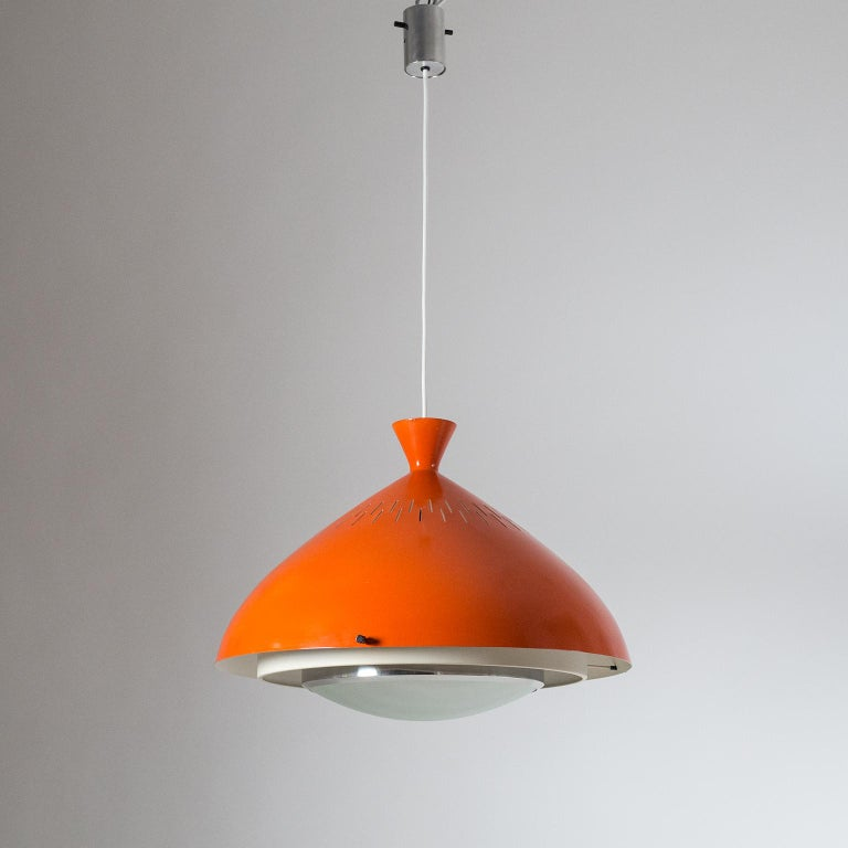 Very rare Stilnovo pendant from the late 1950s. The oversize aluminum shade is lacquered in a strong dark orange on the outside and off-white on the inside. Underneath is a tiered structure of white lacquered and polished aluminum rims with a curved