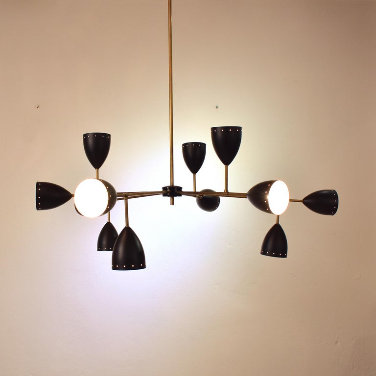 This large Stilnovo style chandelier is very extraordinary. The large scale-brass and black metal lamp shades are going in different directions. It is crafted in Italy in the style of Stilnove from the 1950s.  A unique piece which is a great
