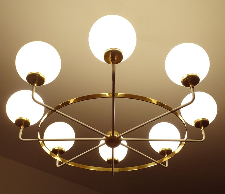 Original 1950s Mid-Century Modern eight-light chandelier in the manner of Stilnovo, featuring a central globe pod with 8 radiating spokes  enclosed with a brass circle ring, opaline glass globes shades on brass cups Dimensions H 23.63 in. x Dm 30.71