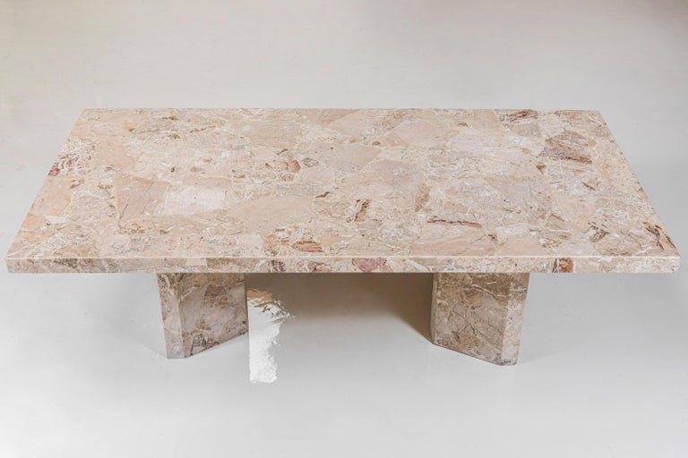 Large matte honed stone rectangular dining table with architectural details. Dining table sits atop two angular bases.