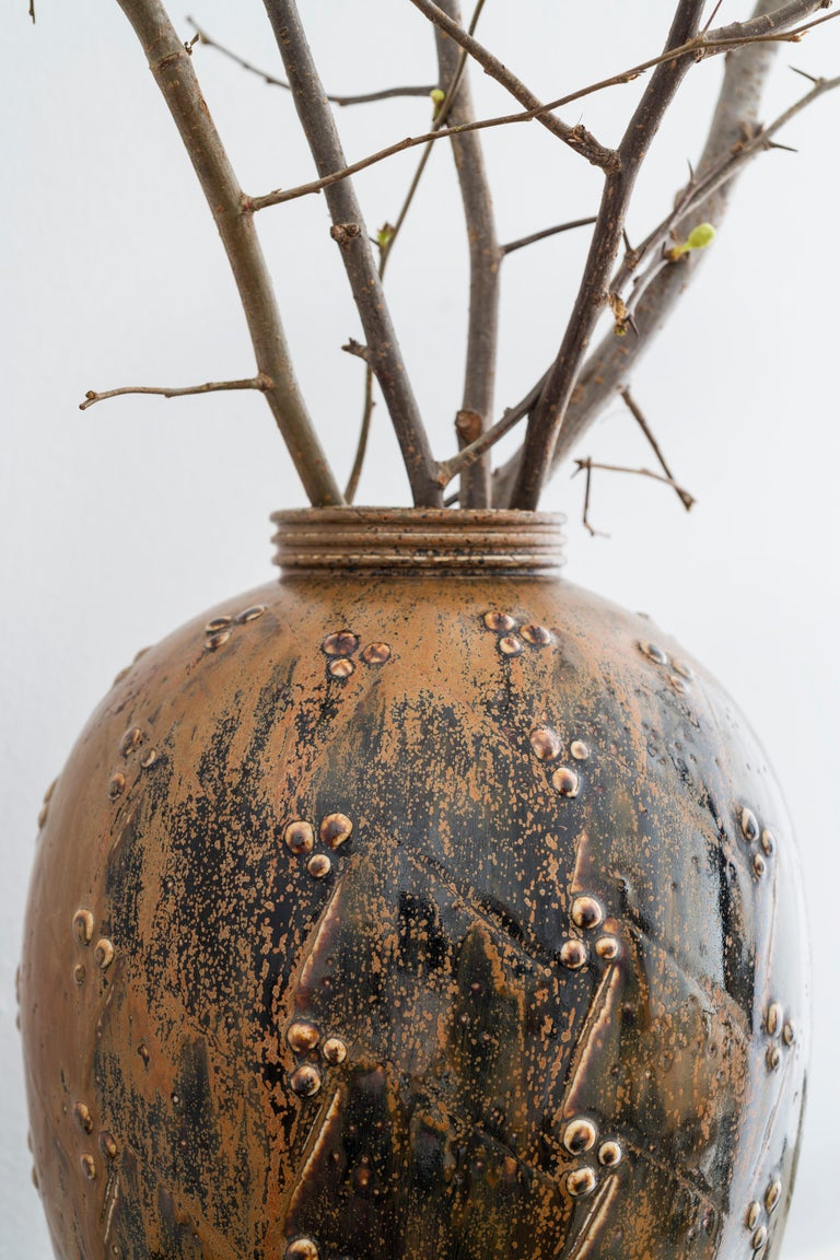 Large stoneware vase by Saxbo with matte rust glaze. There is heavy rust colored glaze on one side while the other side is a mix of black stoneware and rust. 