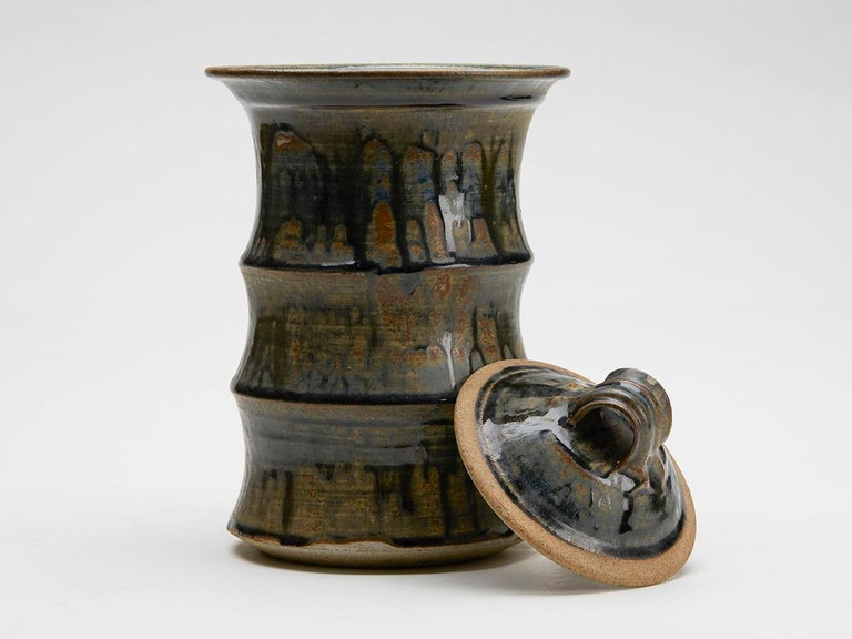 An exceptional and large Studio Pottery lidded jar of cylindrical form in three sections with a wide top rim and recessed domed cover. The jar is decorated with a brown wash applied with blue drip glazes. Despite the quality of this example it is