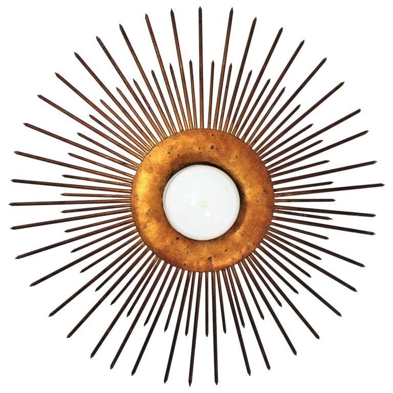 French wrought iron bronze gilt large sunburst flush mount or pendant, 1930s-1940s A highly decorative sunburst shaped ceiling light fixture with frontal light. It has iron nails in two sizes as sun beams surrounding the central sphere and a design