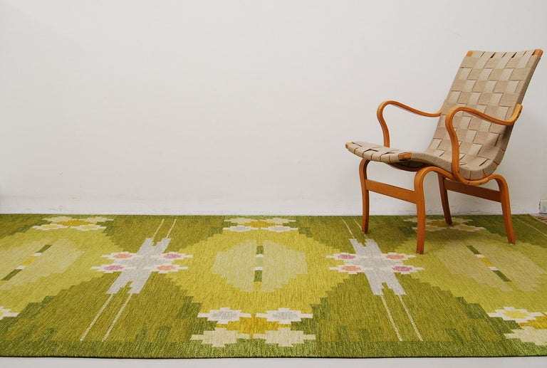 A large flat-weave rölakan carpet designed by Ingegerd Silow, Sweden. Handwoven with a geometric pattern where the colors are different shades of green, yellow, pink and purple. Signed IS in the right hand corner. Professionally hand-washed.