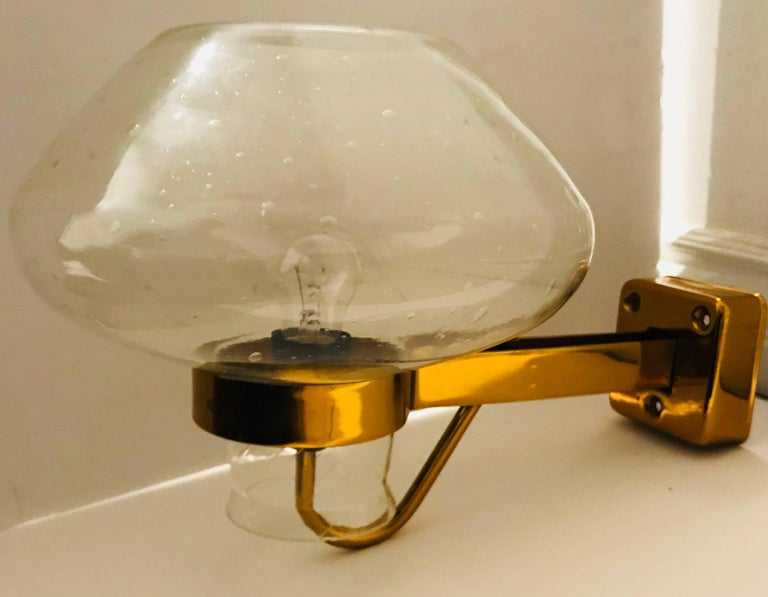 A large indoor or outdoor Swedish wall light composed of a golden enamel brass fixture and a clear bubbled glass shade. Designed by Gunnar Asplund for ASEA. Newly rewired. A pair available if needed.