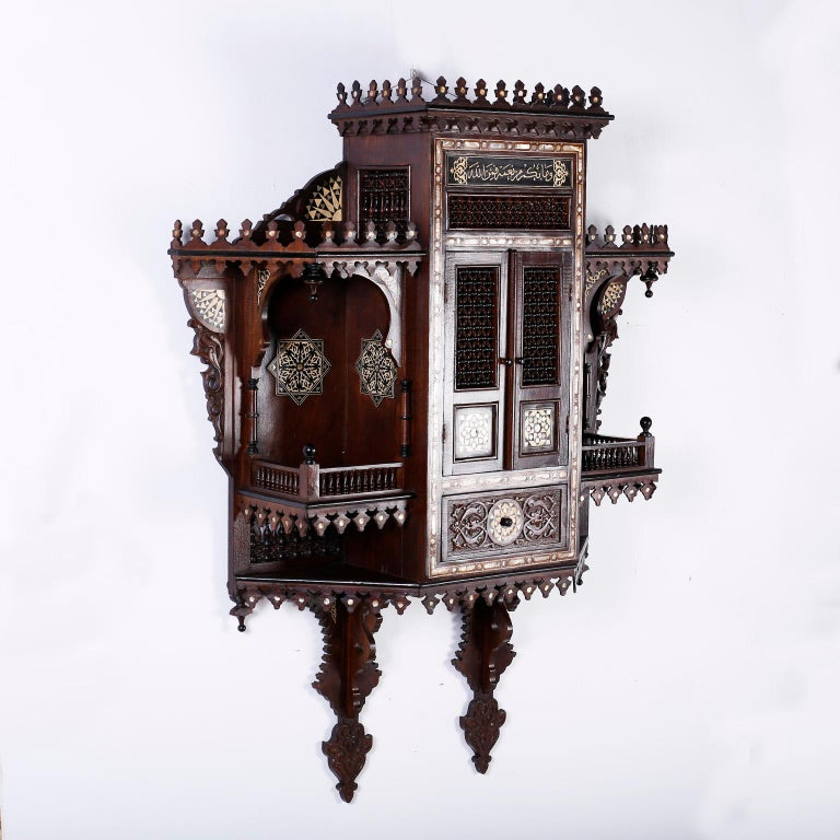 Refined antique Syrian hanging wall cabinet crafted in mahogany and featuring turrets, Moorish arches, columns, balistrades, inlaid mother of pearl, ebony and bone medallions, floral carvings and an overall generous scale. Best of the genre.