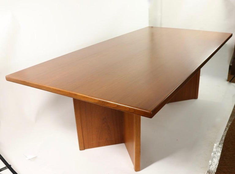 Spectacular conference, or dining table having a solid teak top, and opposing V shaped pedestal legs.