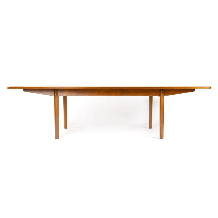 A large Scandinavian Modern dining table or conference with a bowed top crafted in solid teak wood on oak tapered dowel legs. 110.5