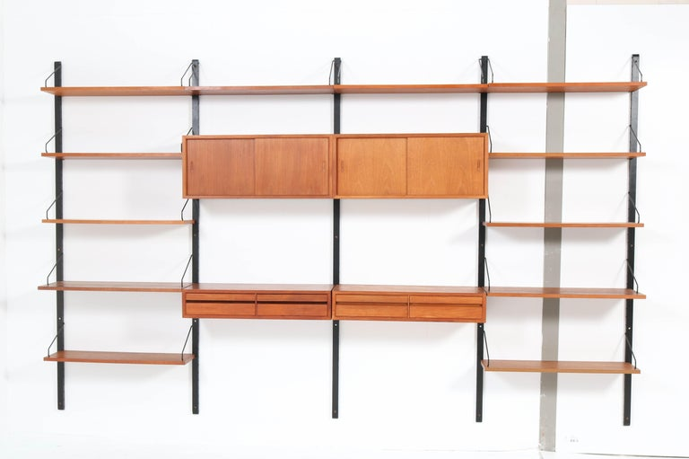 Magnificent large Mid-Century Modern teak wall unit. Design by Poul Cadovius for Cado. Striking Danish design from the 1950s This wonderful wall unit consists of 5 black lacquered wooden uprights H 202 cm or 2 cabinets with sliding doors: H