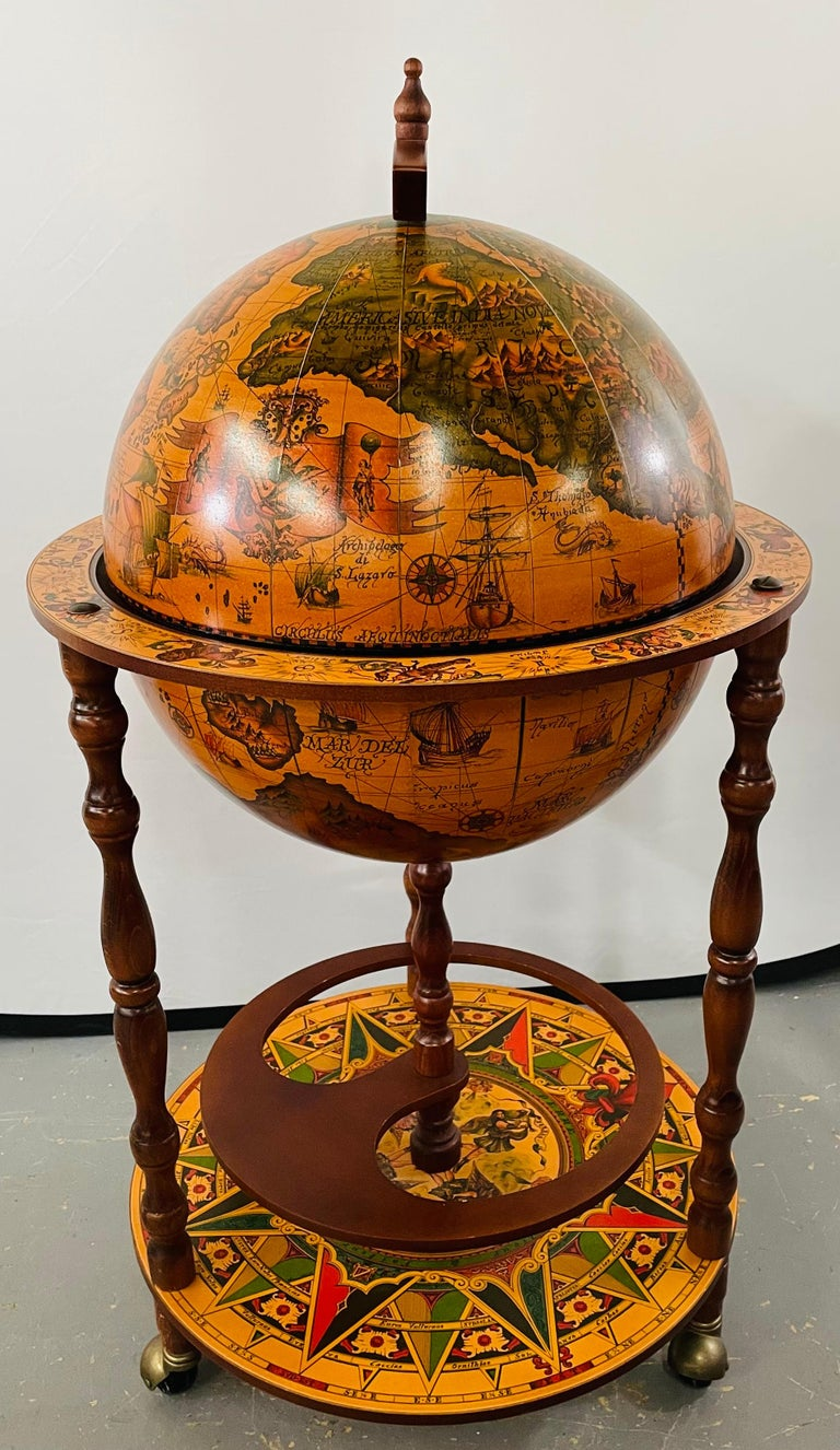 An exquisite late 20th century vintage large terrestrial and celestial globe with astrological signs displaying magnificent details made of mahogany wood and papier-mache and standing on a round zodiac platform attached to 4 wheels with brass