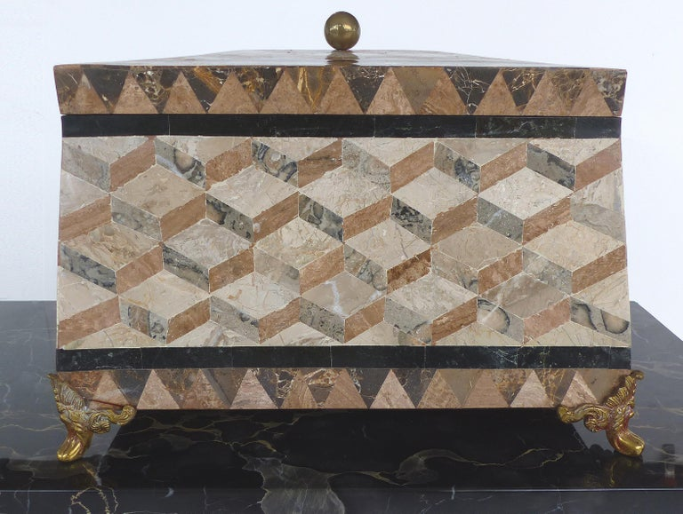 Offered for sale is a large tessellated marble hinged lidded box from Maitland-Smith. This elegant box has intricate over-all patterns with angled sides and top. The lid is opened with a brass ball finial and the base is supported by ornate brass