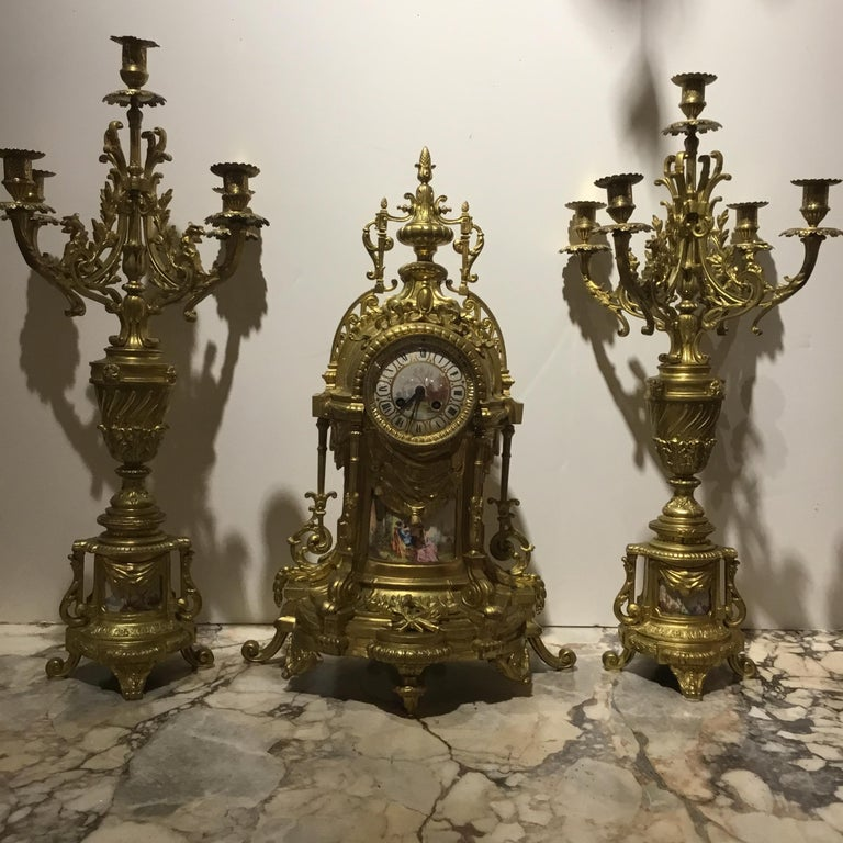 Louis XVI style garniture set. Torch and quiver design centered at the Bottom of the clock. A hand painted garden scene is presented at the Lower portion of the clock and a beautiful hand painted face depicts The French landscape. An urn is