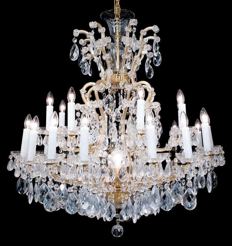 A large two-tier, twenty four light glass and brass 20th century chandelier in the neoclassical style. The upper tier has eight brass scrolling branches the lower with sixteen, all enhanced with multiple florets, issuing from an ornate brass bowl
