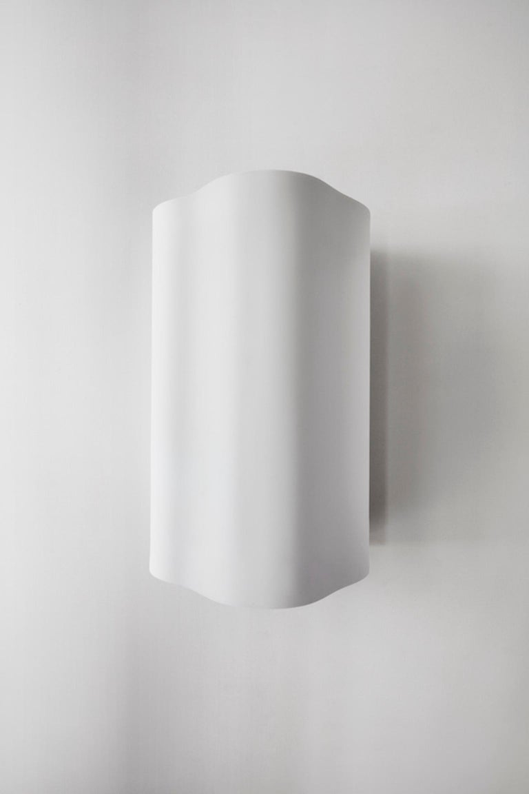 Part of the Barcelona series, sconce II, inspired by elements experienced in Richard Meier's iconic Barcelona Museum of Contemporary Art. An ample body and harmonious curves define this wave-like light, hand sculpted in matte white Corian.  LED