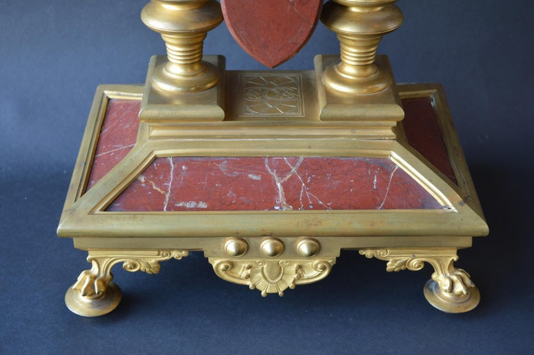 Large unusual French Neo-Grec Revival gilt bronze mounted marble mantel (fireplace) clock, circa 1870. The shaped rouge griotte marble arched case centering a circular dial with gilt Roman chapters and steel Breguet hands above twin key escapements,