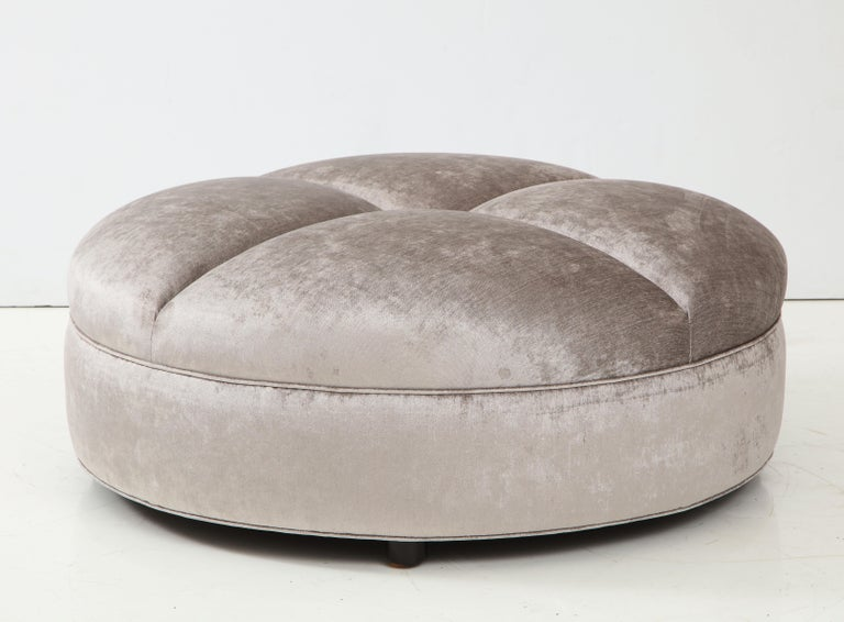 The oversized ottoman has been beautifully reupholstered in a luxurious silvery grey velvet fabric and sits up on four barrel shaped feet.