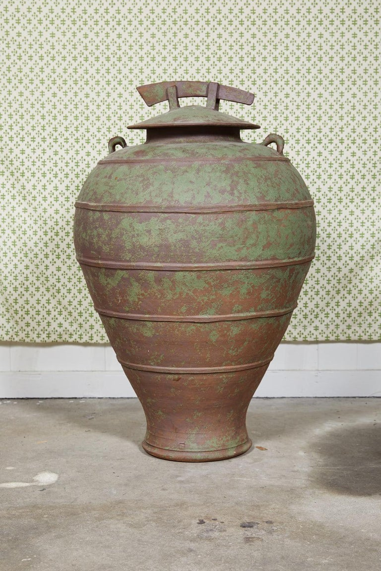Large urn shaped clay jar with ornamental lid having a bronze and green patina and stamped by the maker. The jar has a pair of handles near the mouth of the vessel, attractive horizontal ribbing, and a decorative drain hole at it's tapered base.