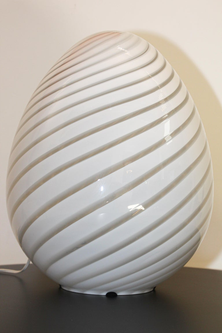 Stunning large swirled glass lamp by Vetri murano egg lamp. Amazing large scale Modern Egg-shaped white Murano glass table lamp light by Fulvio Bianconi for Venini in the sensual shape of an egg having the classic swirl pattern lines in the glass.