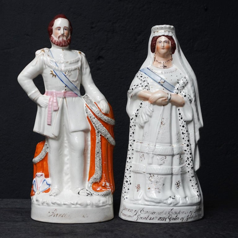 Set of 19th century ceramic Victorian Staffordshire figurines of Queen Victoria and Prince Albert. Each with gilded trim and polychrome enamels.  Antique Queen Victoria of England ceramic Victorian figurine.  The gold gilt script on Victoria's base
