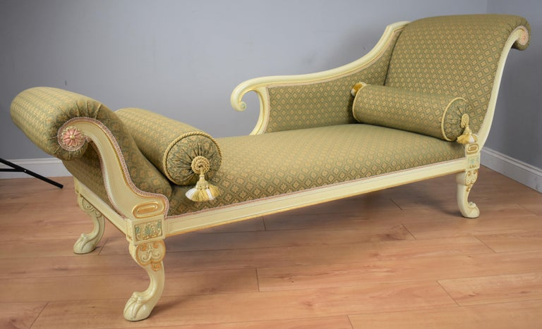 20th century large Victorian style painted chaise lounge in very nice condition with scroll ends with detailed flower to centre standing on claw feet. The upholstery is in good condition having been recently upholstered in a green patterened fabric,