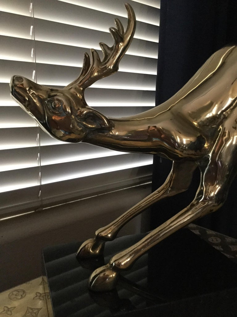 A rare vintage brass animal statue from 1980s. Newly polished. Jumping reindeer appears to be in flight attached to the marble base.