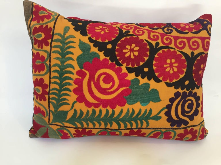 Large vintage colorful Suzani embroidery lumbar pillow red with colorful threads.  A reddish embroidered pillow with flower motifs in shades of black, red, yellow, white, green, magenta, with linen backing and zipper in the back.  The pillow is made