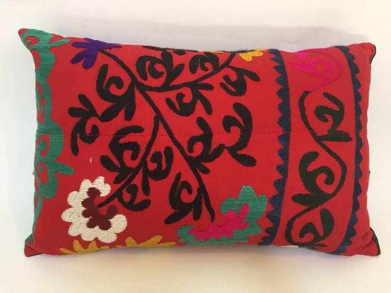 Large vintage colorful Suzani embroidery lumbar pillow red with colorful threads.  A reddish embroidered pillow with flower motifs in shades of black, red, yellow, white, magenta, kelly green, with linen backing and zipper in the back,.  The pillow