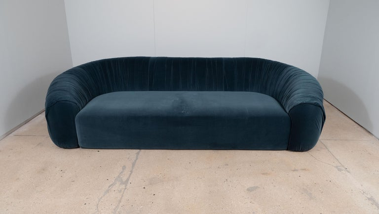 Unique in its craftsmanship and design, this vintage Italian sofa consists of a single long seat with a single low back which curves around the sides. A double chrome metal brace runs along the width of the back and sides, giving it a sophisticated