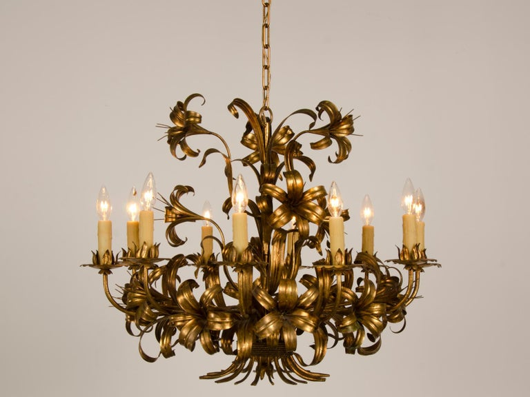 A fabulous vintage French tôle chandelier of gilded iron in the form of a lavish bouquet of lilies and leaves and stems from France circa 1940 with ten lights. This gorgeous chandelier is modeled after the famous fixtures created of painted metal