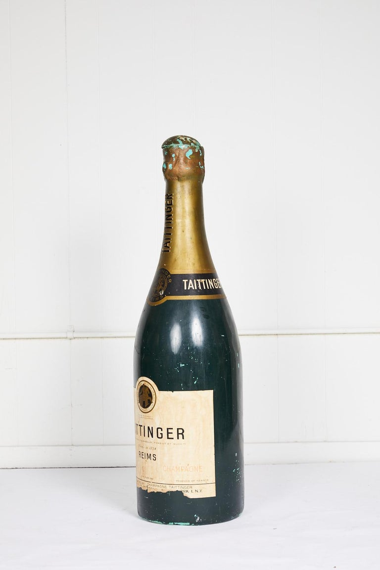 20th century vintage French Taittinger champagne bottle made of composite material and used as an advertising prop. The bottle top has been cut open.
