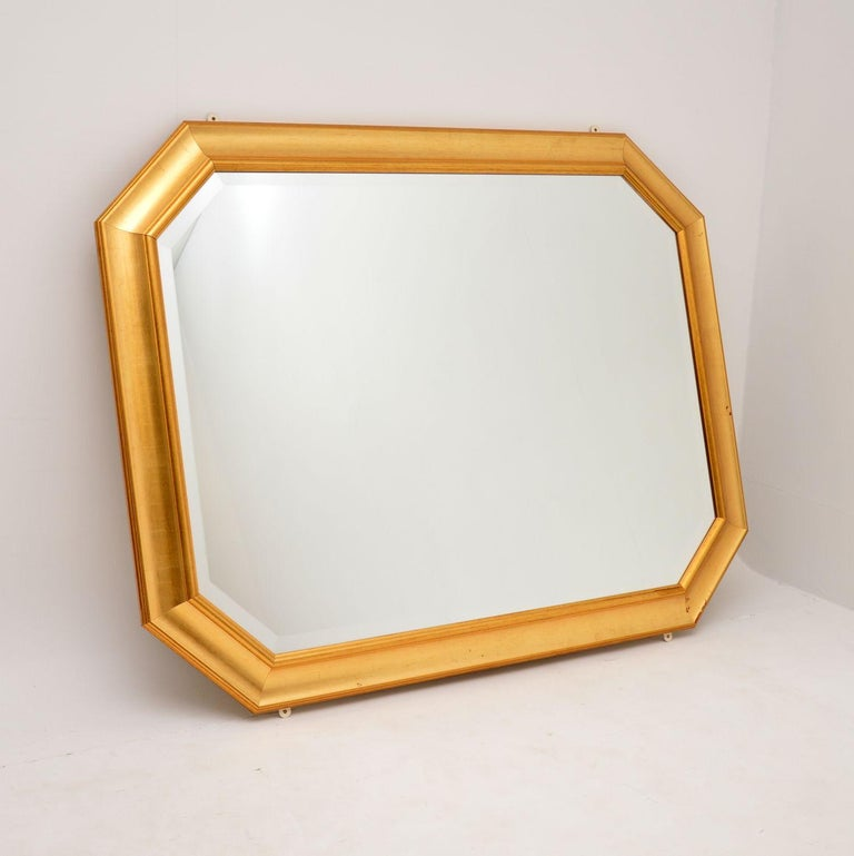 A fine quality and very large vintage gilt wood mirror. This was made in England, it dates from around the 1970-80's.  This is beautifully made and is very impressive. It has bevelled glass which is in great condition. The gilt wood frame is