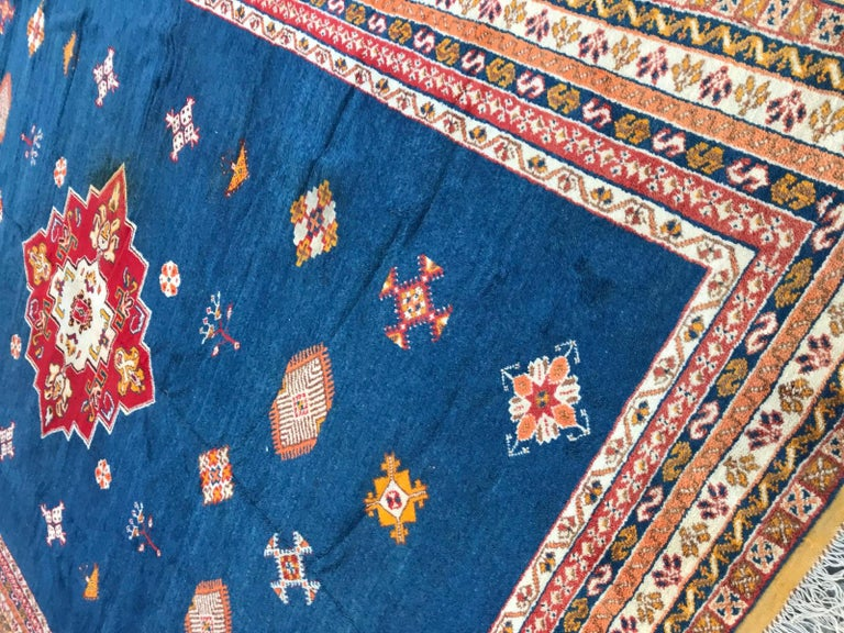 Nice large midcentury Berbere Moroccan rug, with beautiful tribal design with a central medallion and beautiful colors with blue field and red, green and orange, entirely hand knotted with wool velvet on wool foundation.