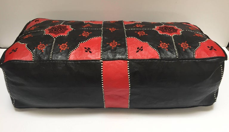 Large red and black hand tooled leather Moroccan ottoman. Rectangular shape Moroccan pouf in red and black leather embroidered with black and white silk threads. Handcrafted by skilled artisans in Marrakech.