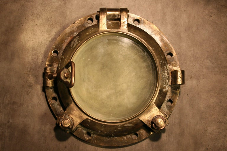 Tilting, signed marine window equipped with a hinge, two screw bolts and a handle with a lock for a safety cover. The base ring has eight mounting holes and original glass with a thickness of 2.5 cm. There are visible scratches and small chips on