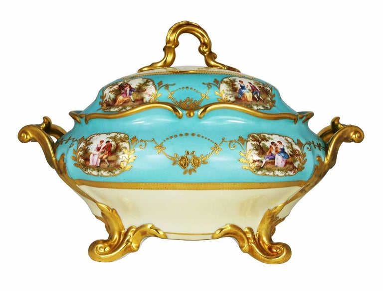 A large beautiful vintage porcelain tureen with under-plate in Celeste blue with gold painted decoration. The tureen has four romantic courtship scenes on the body and four on the lid, along with gold painted floral swags and beading. Handles, legs,