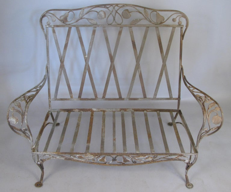A large and rare Saltertini wrought iron settee, with a beautiful decorative motif on the arms, skirt, and seatback of large pears and apples. In original condition, can be stripped and restored if desired.