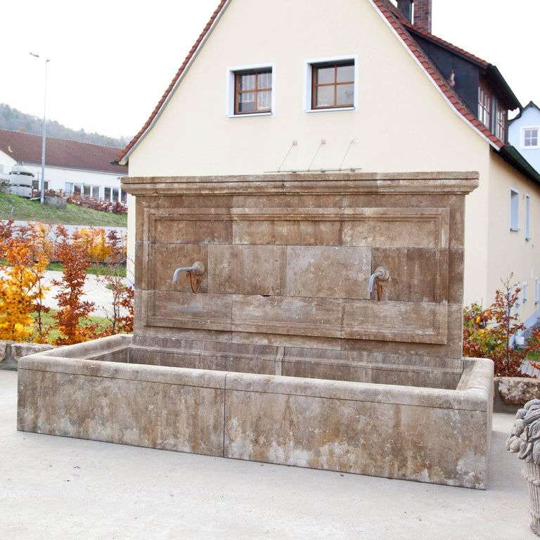 Large blue stone wall fountain with rectangular basin. The back wall is architecturally structured and equipped with two spouts. Measures: Basin height 50 cm.