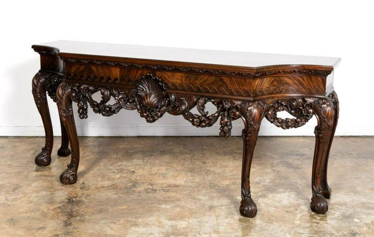 A Fine and well carved English mahogany console table in the George II style having a breakfront form with large scallop shell, the apron with floral and fruit swags, and rising on cabriole legs with acanthus decorated feet. England, circa