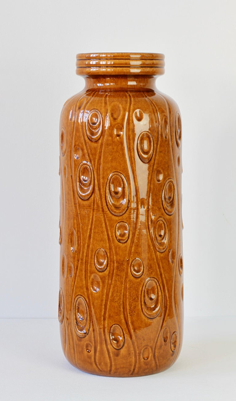This tall collectable midcentury vintage floor vase was produced circa 1965 by the renowned producer of West German pottery - Scheurich Keramik. The vase features the 'Koralle' (Coral) relief pattern in a lovely amber brown color high gloss glaze.