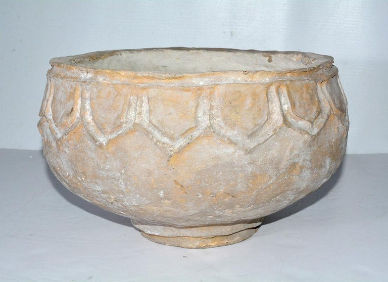 The large white-washed terracotta like pot or urn is made of paper mache.  pot has a leaf-like design around the rim and is handmade and lightweight.   The pot or bowl will make a wonderful centerpiece on a dining table, kitchen or console table.