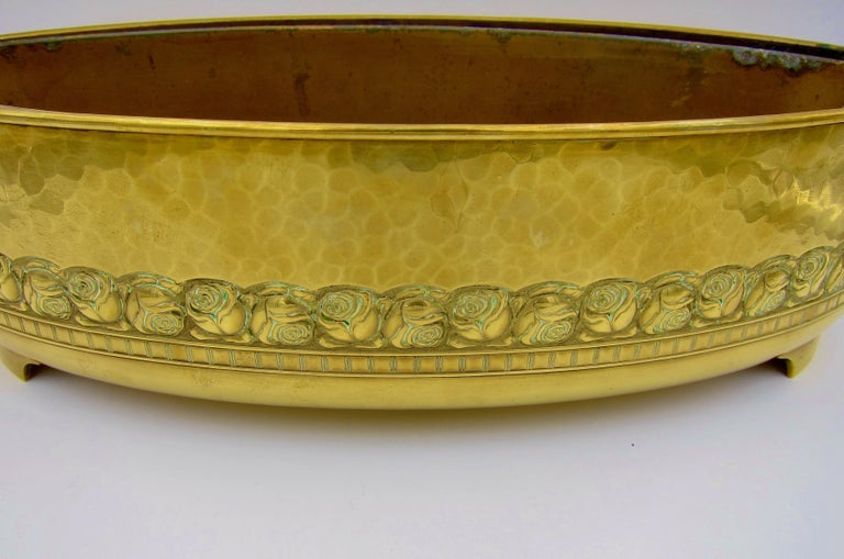 An early 20th century large oval planter of golden yellow brass resting on two cast feet manufactured by WMF (Württembergische Metallwarenfabrik) of Geislingen, Germany for export to France, dating circa 1910. The sturdy antique planter is an