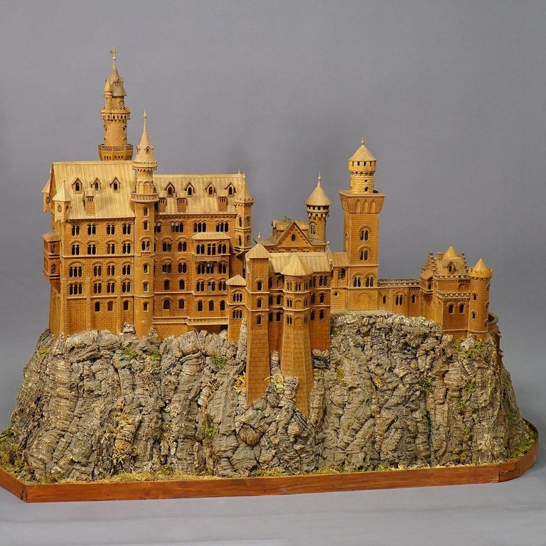 A large model of the fairy-tale castle of king ludwig II of bavaria. The wooden carved model was made in the first half of the 20th century. It is a livelike model with several very detailed decorations. Inside with illumination.  Measures: width